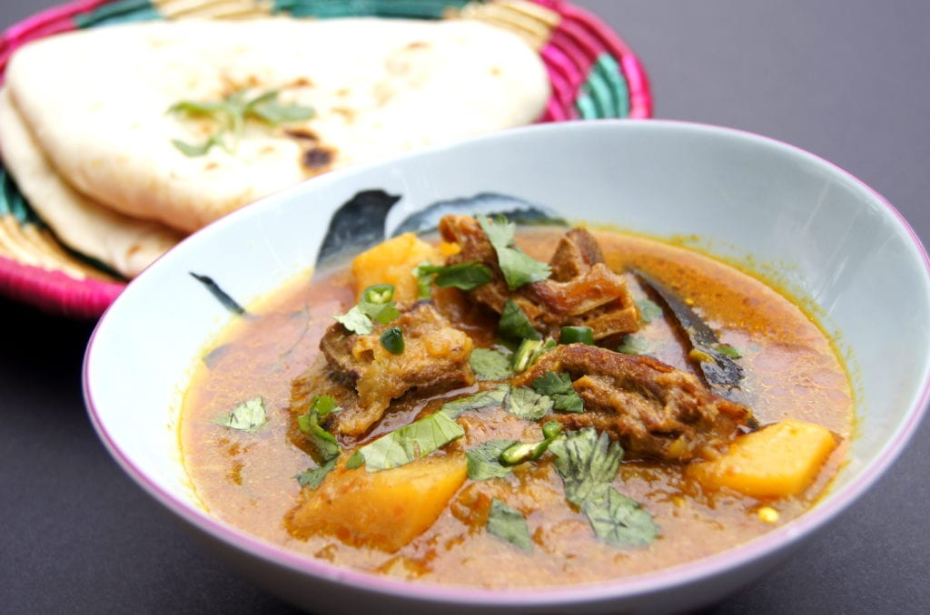 Bowl of Mutton and Potato Curry with naan in the background.