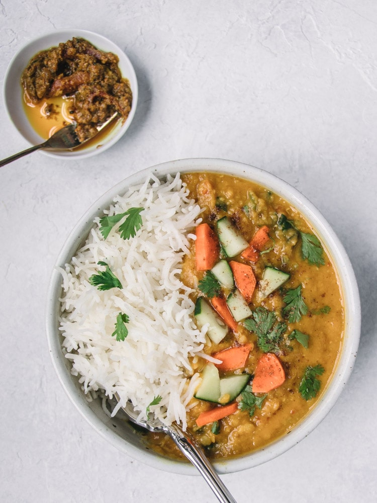 Masoor Dal in a white bowl with rice on the side and carrots and cucumbers on top