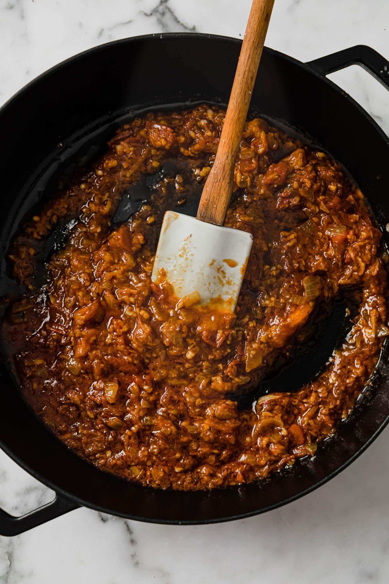 Sauteed tomato and onion masala for baingan bharta in a black pan with wooden spatula