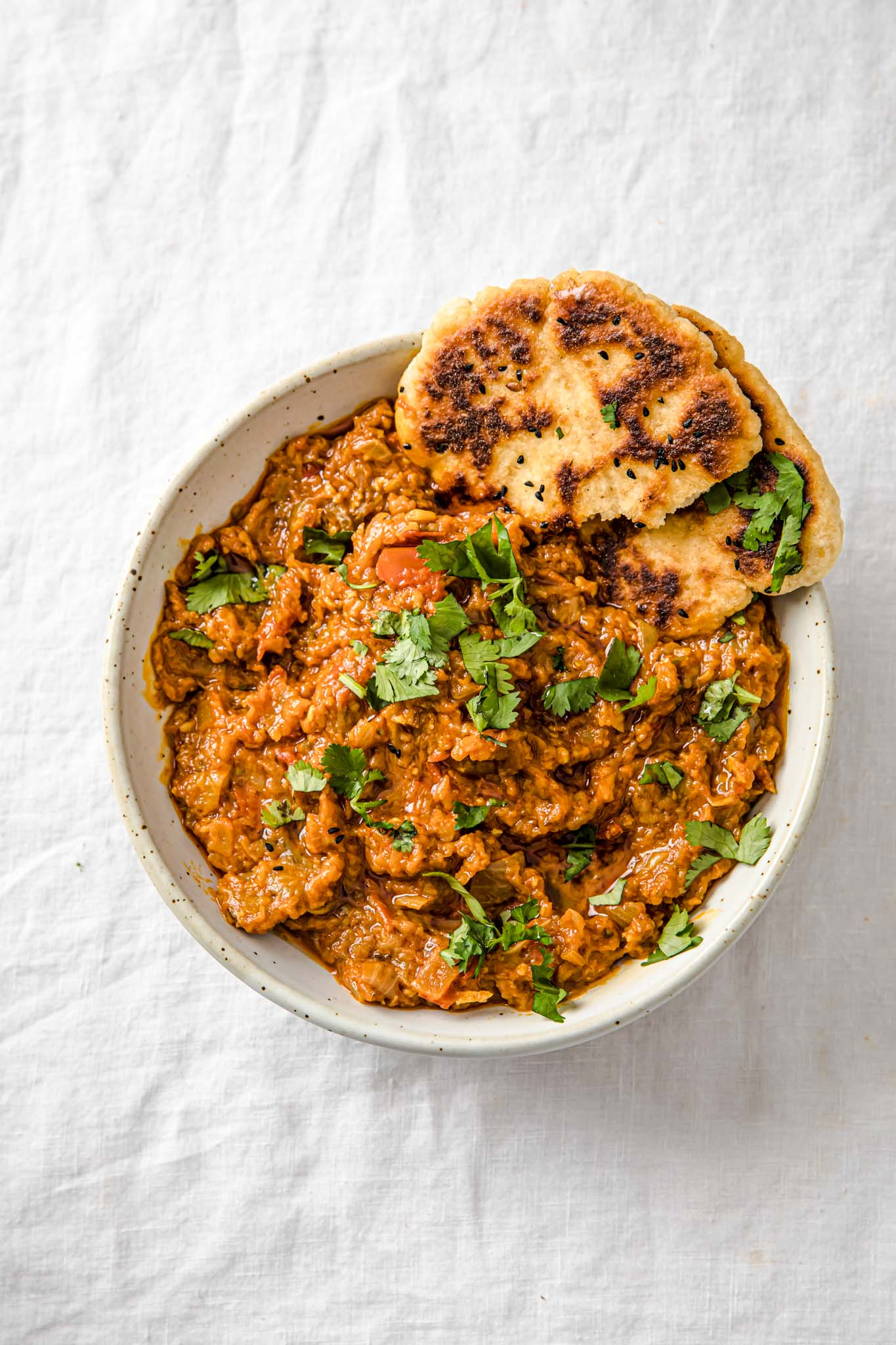 Baingan Bharta (Oven-Roasted Eggplant Curry) in a speckled bowl with naan and garnished cilantro