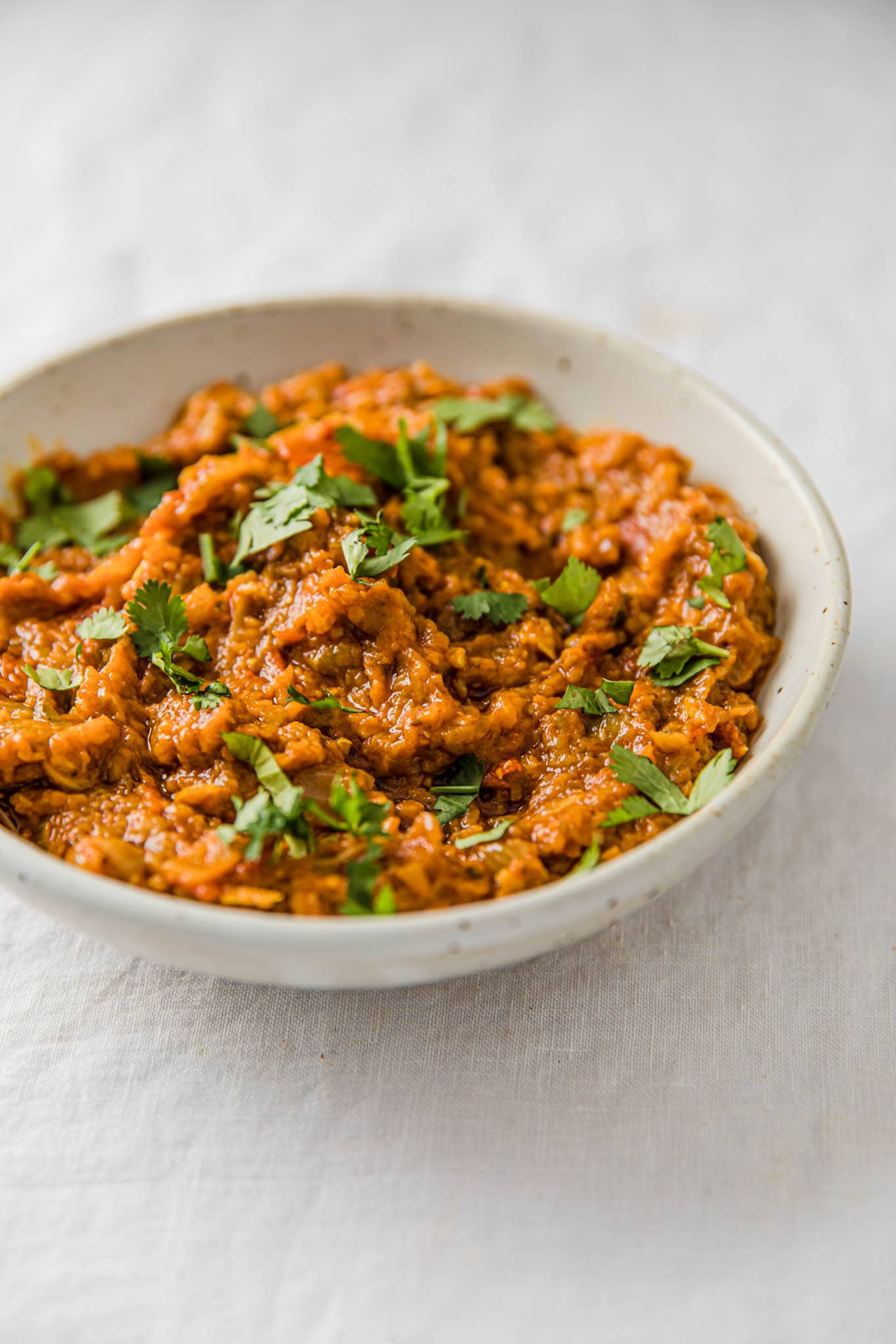 Baingan Bharta in a speckled bowl garnished with cilantro