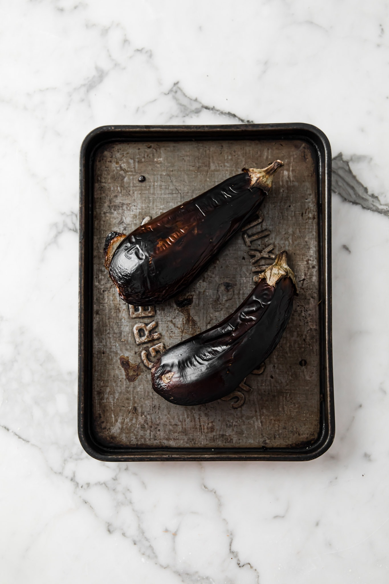 Oven Roasted (broiled) eggplants with charred skin on a sheet pan right