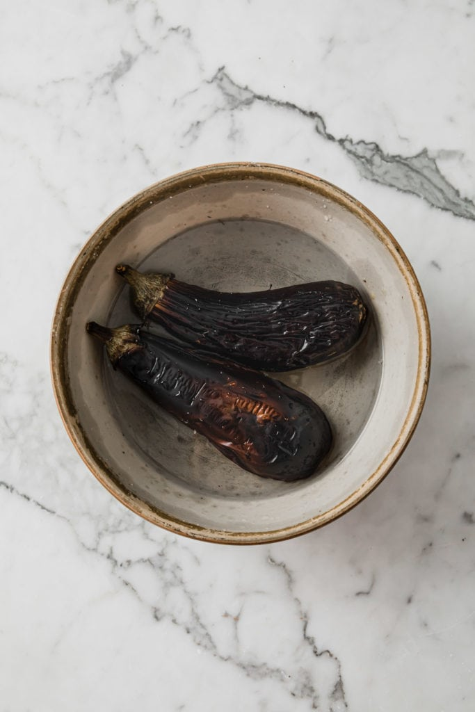Oven-Roasted (broiled) eggplants with charred skin in a bowl
