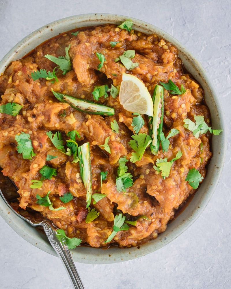 Top down close up of a bowl of Baingan Bharta (Smoked Eggplant Curry) garnished with a lemon wedge, green chilies and cilantro.