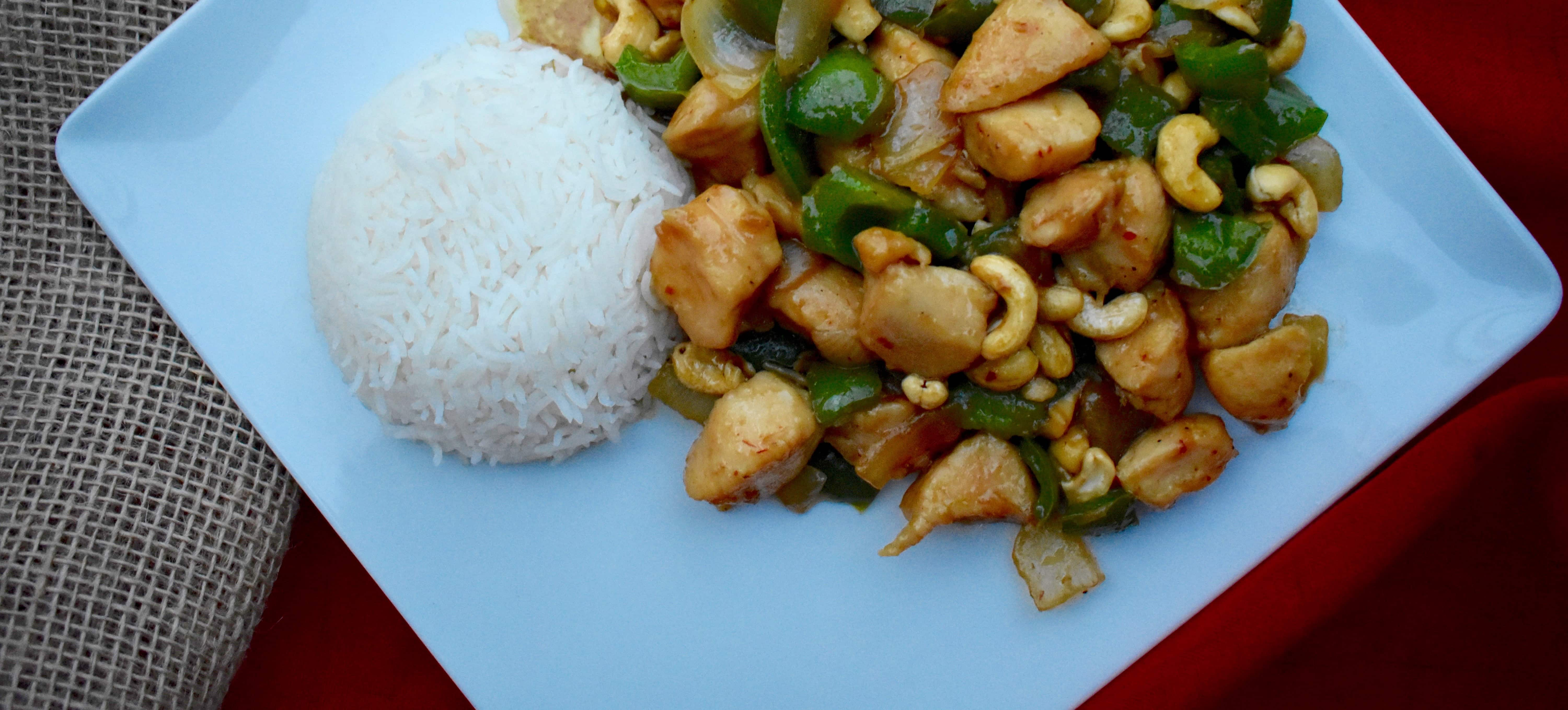 Pakistani -Style Chinese Chicken with Cashews on a white plate with some white rice.