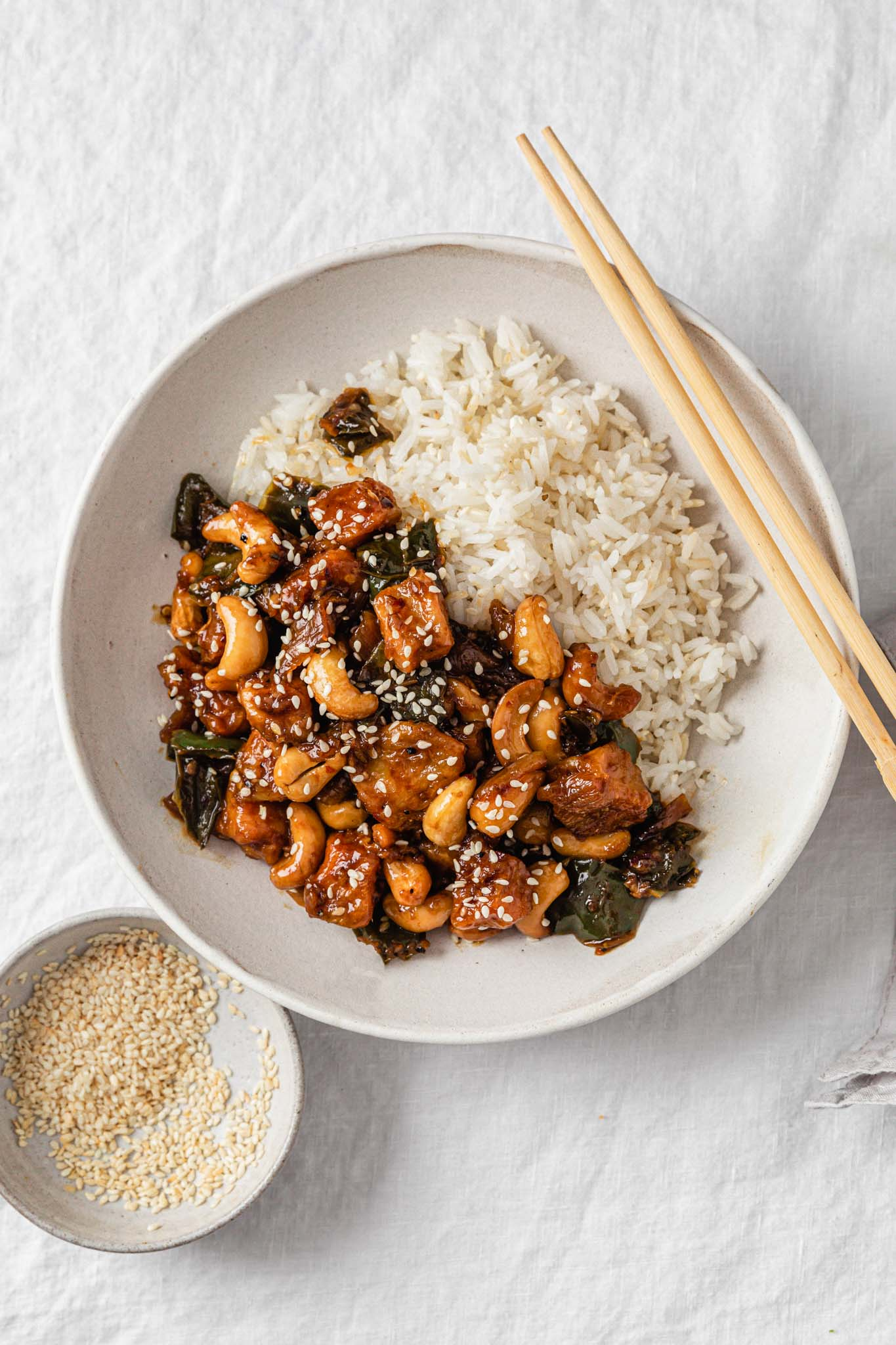 Spicy Cashew Chicken in a bowl with rice with chopsticks and sesame seeds on the side