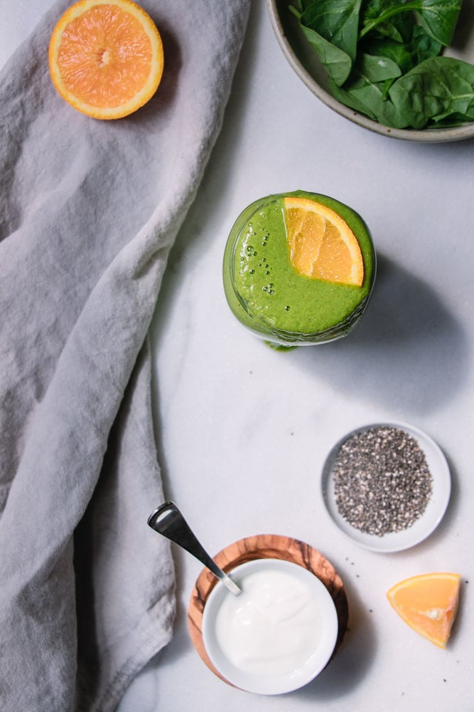 Spinach leaves, chia seeds, yogurt and slice of orange next to a glass mason jar filled with Iron-Boosting Orange Green Smoothie which is topped with a slice of orange.