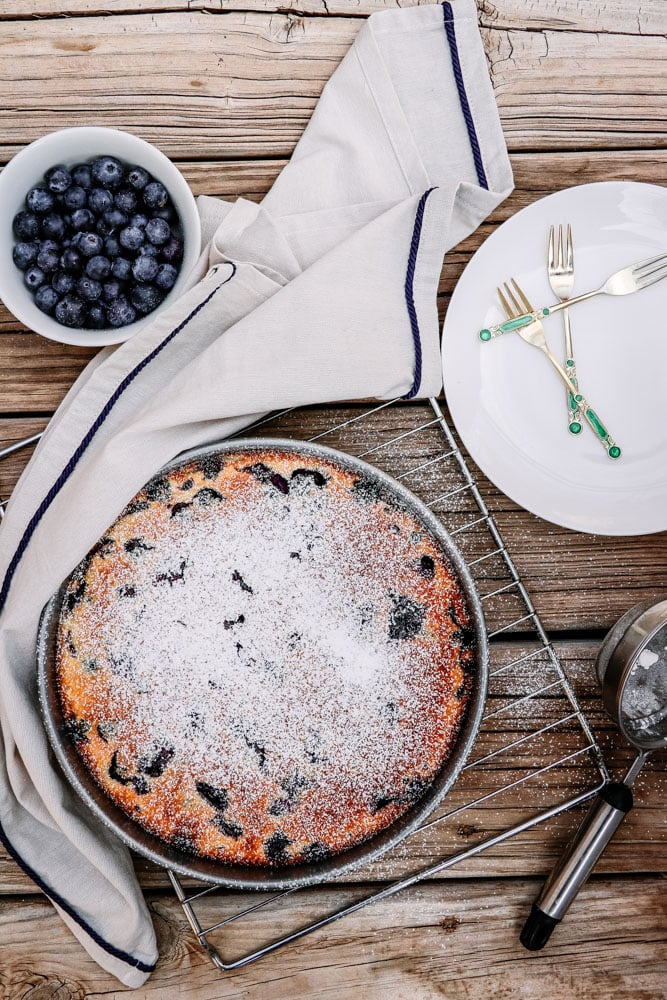 Gluten-Free Blueberry Lemon Clafoutis dusted with powdered confectioners sugar in a baking pan.
