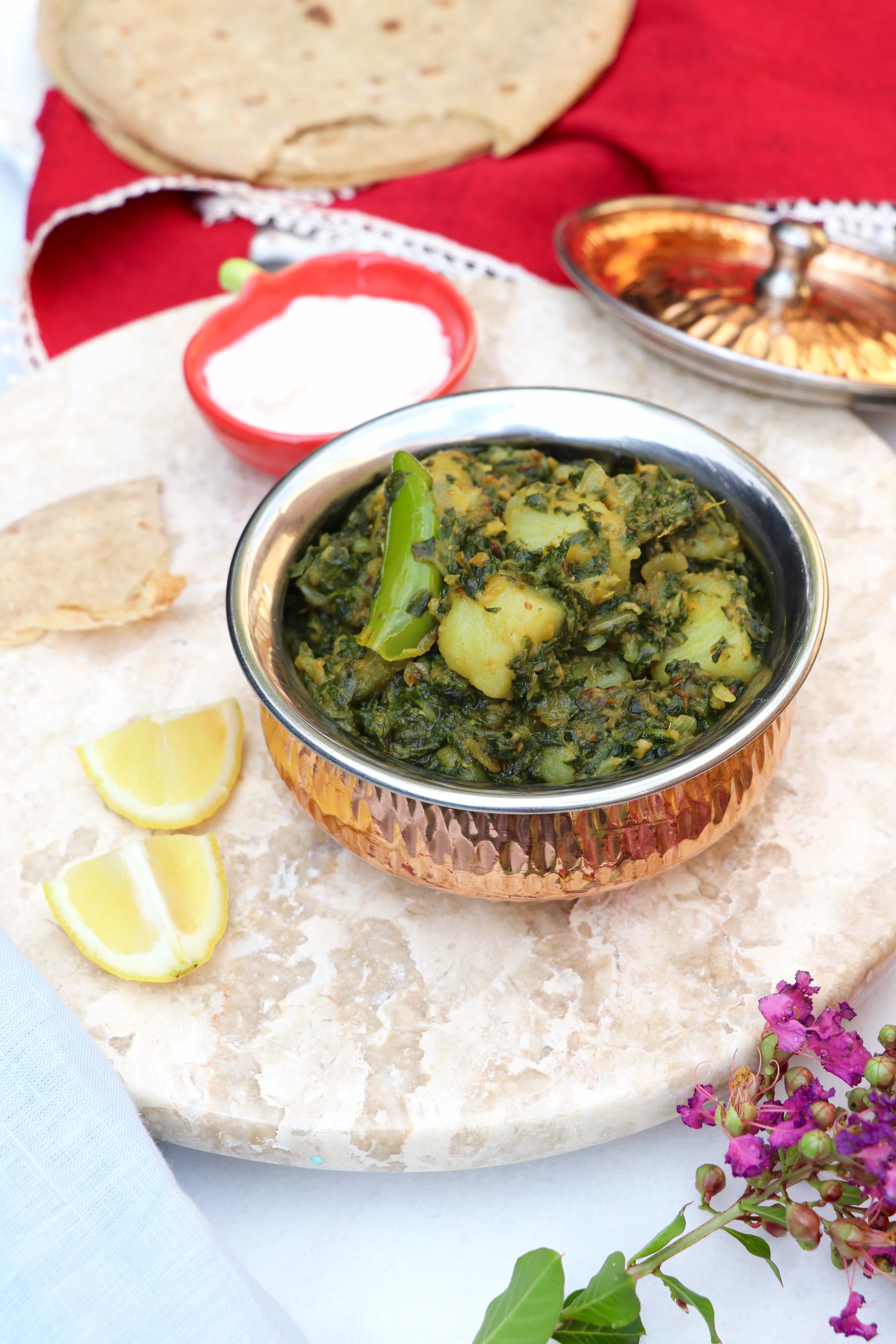 Spinach and Potato Curry (Aloo Palak) in a bowl with lemon wedges and roti on the side