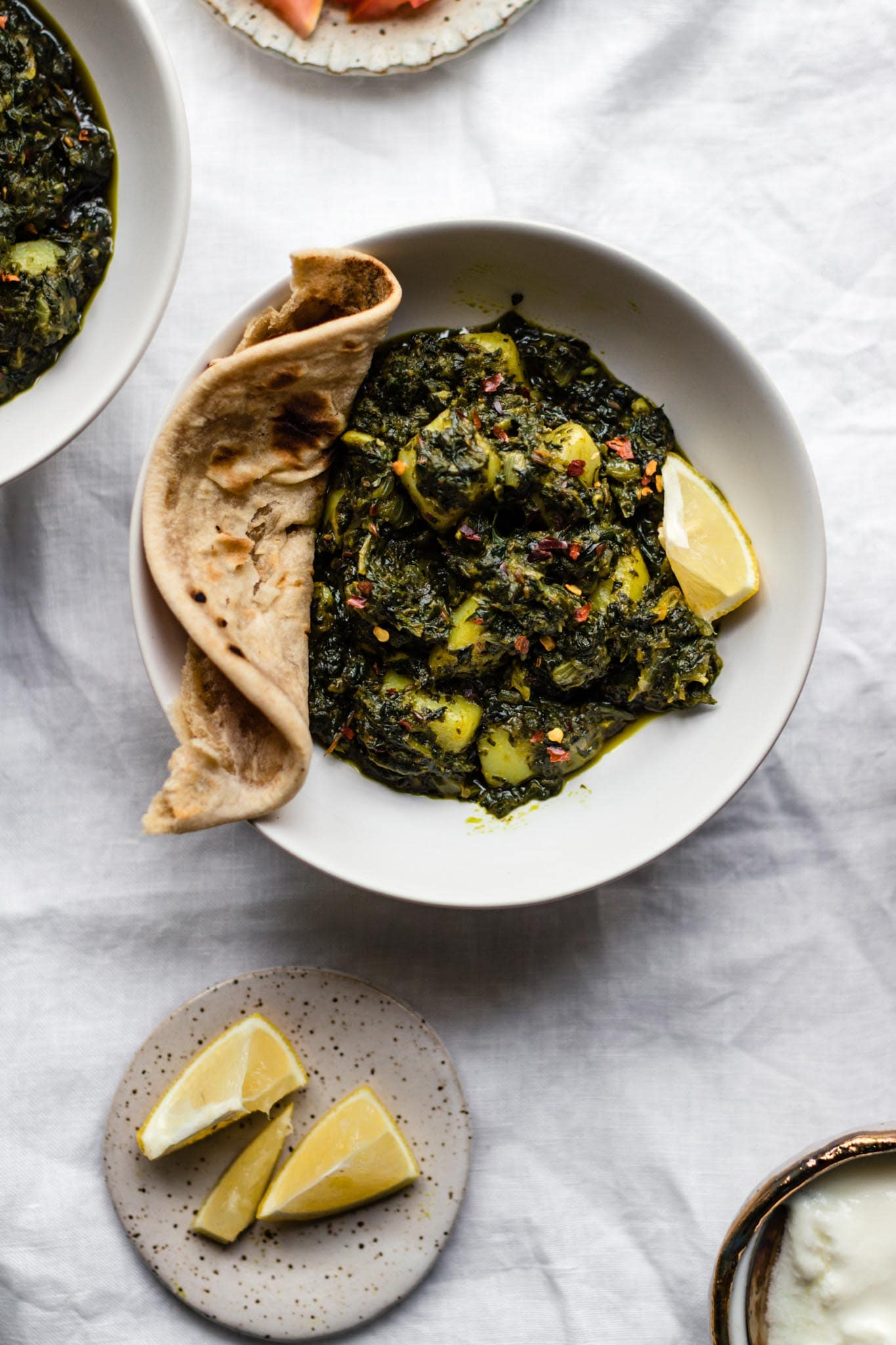 A bowl of authentic Spinach and Potato Curry (Aloo Palak) with roti
