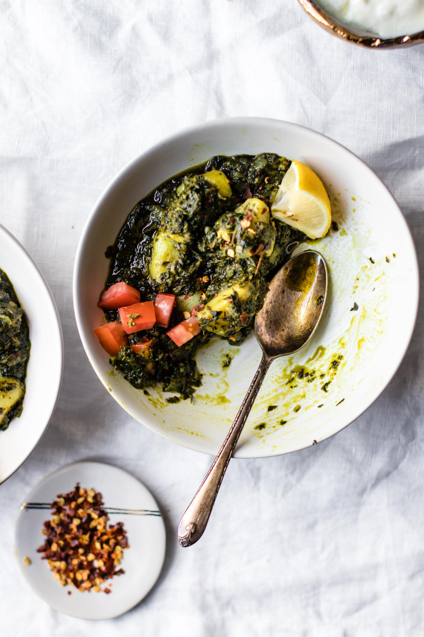 A white bowl of Spinach and Potato Curry (Aloo Palak) with a silver spoon