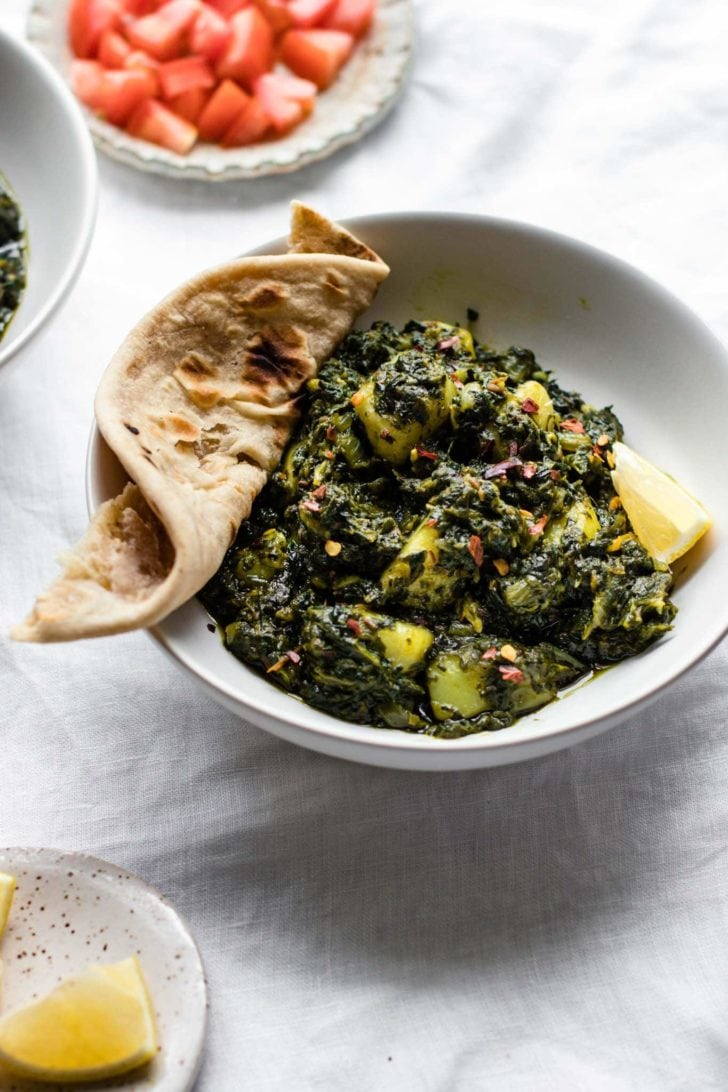 Spinach and Potato Curry (Aloo Palak) in a white bowl with roti