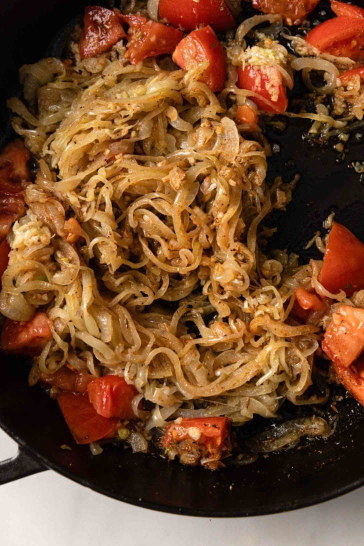 Chopped tomato added to sauteed onions