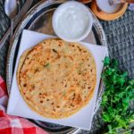This image shows mooli wala paratha on a plate with a bowl of yogurt