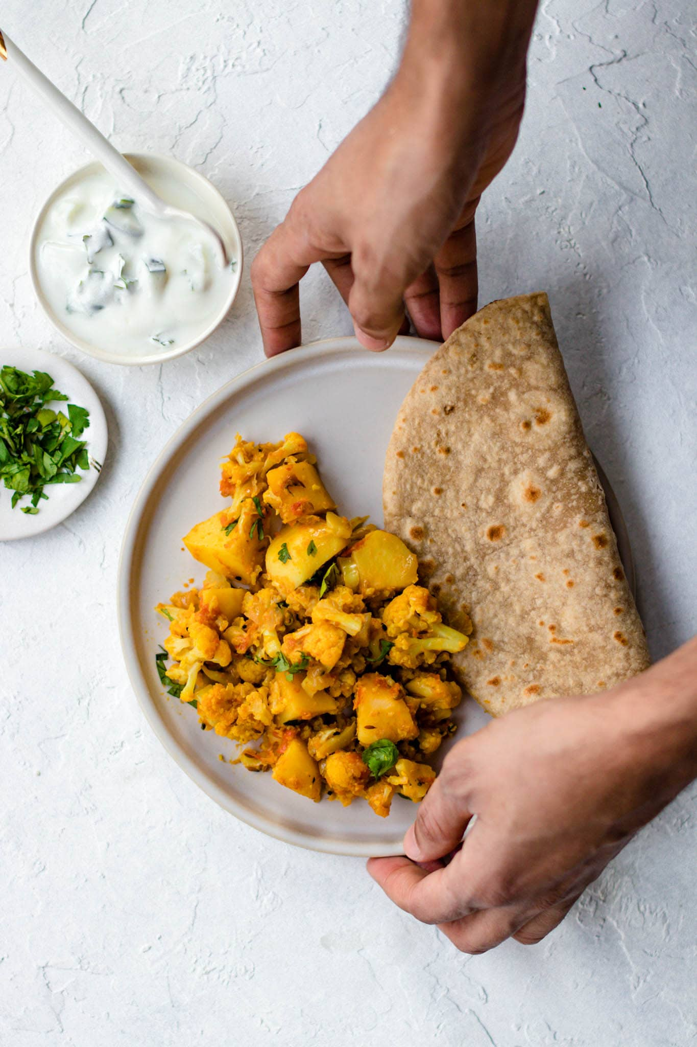 Holding a round plate with Aloo Gobi and a folded piece of roti.