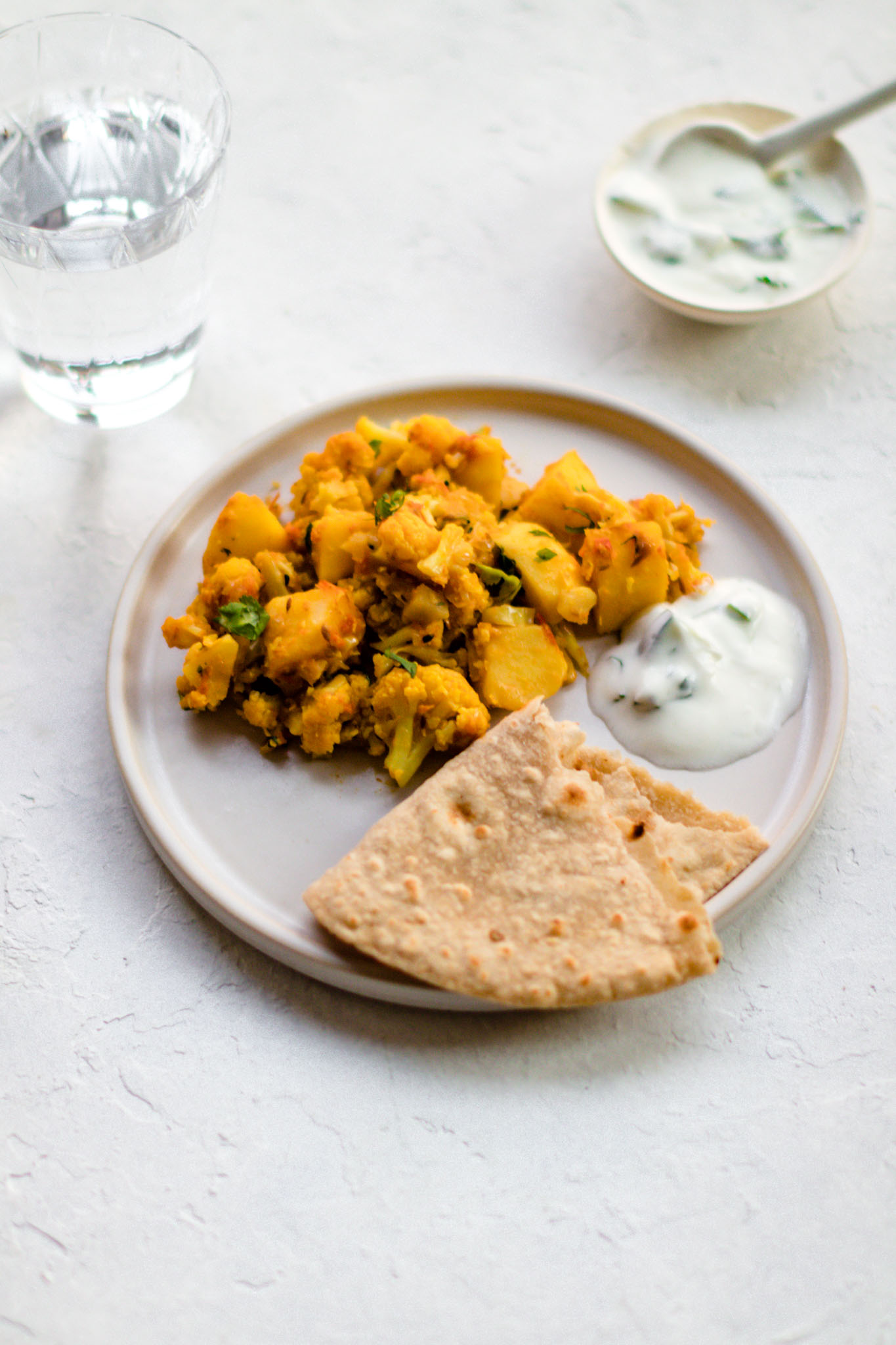 A round plate with Aloo Gobi, raita and a piece of roti.
