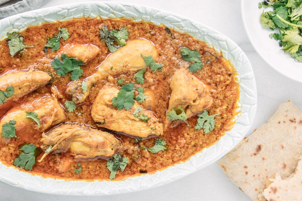 A plate of Authentic Chicken Korma garnished with cilantro.