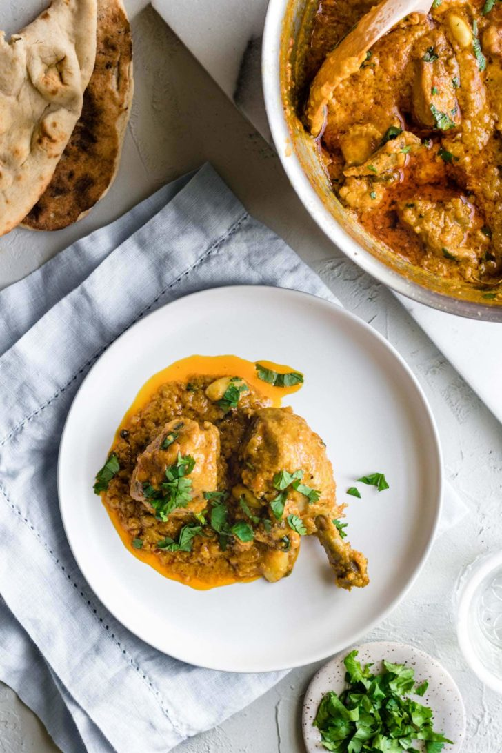 Chicken Korma on a white plate with naan on the side.