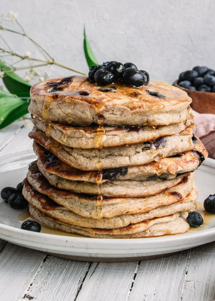 A stack of Gluten-Free Blueberry Pancakes topped with blueberries and drizzled with maple syrup on a white plate.