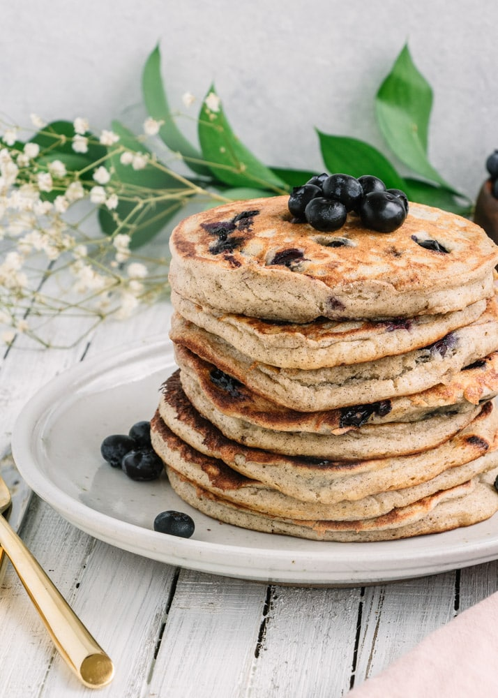 A stack of Gluten-Free Blueberry Pancakes topped with blueberries on a white plate.