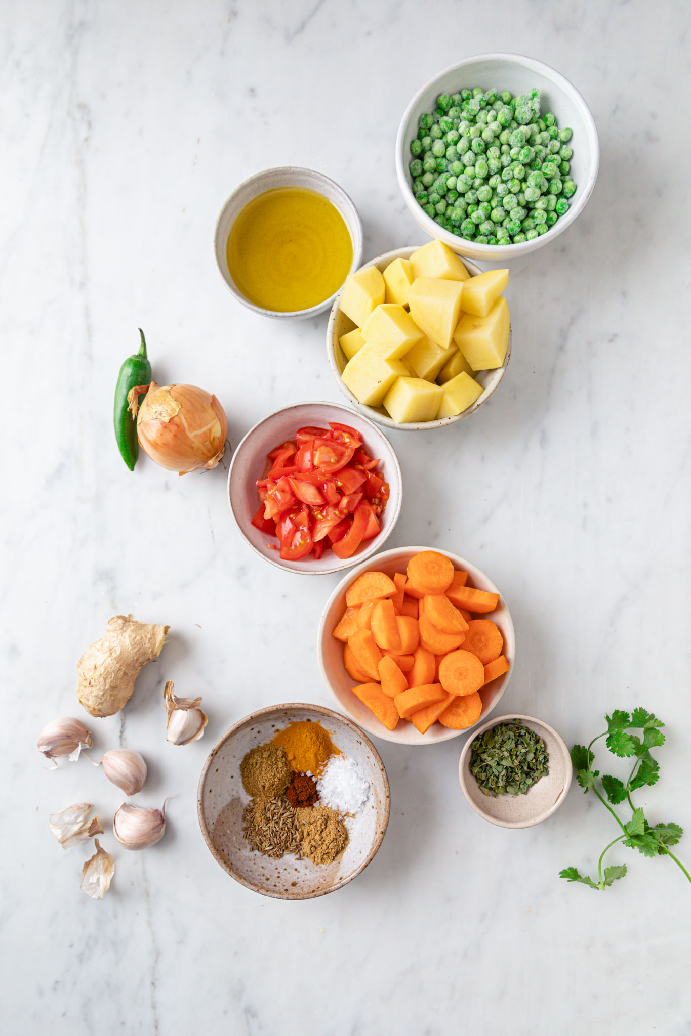 Ingredients for making Mixed Vegetable Curry on a marbled surface