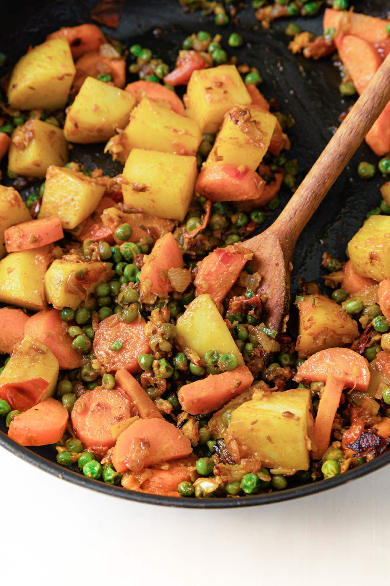 Potatoes, carrots, and peas in a black pan with a wooden spoon