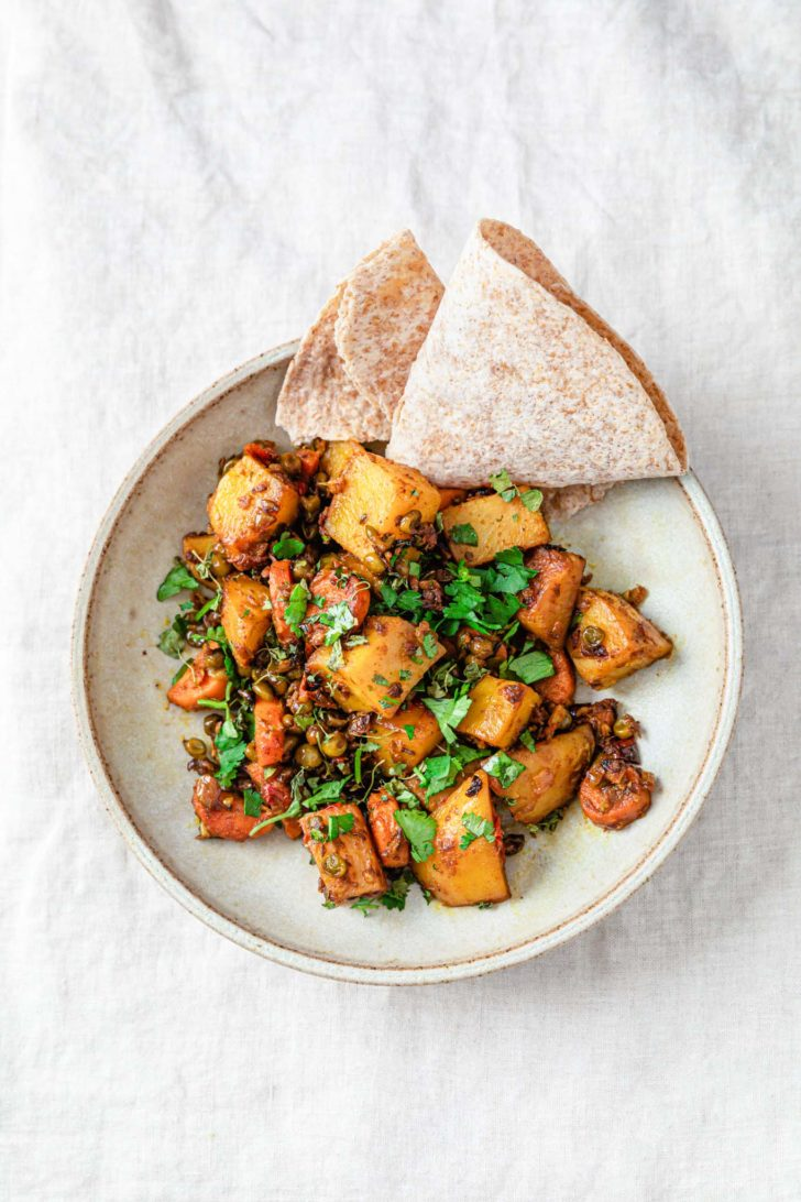 Mixed vegetable curry with potatoes, carrots, and peas in a bowl sprinkled with cilantro and served with roti.