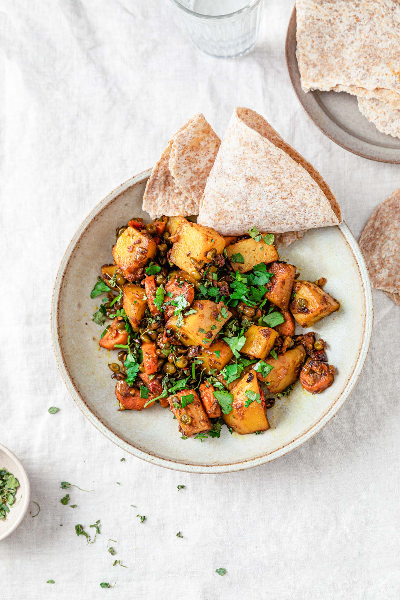 Mixed vegetable curry with potatoes, carrots, and peas topped with cilantro in a beige bowl next a small bowl of methi (dried fenugreek).