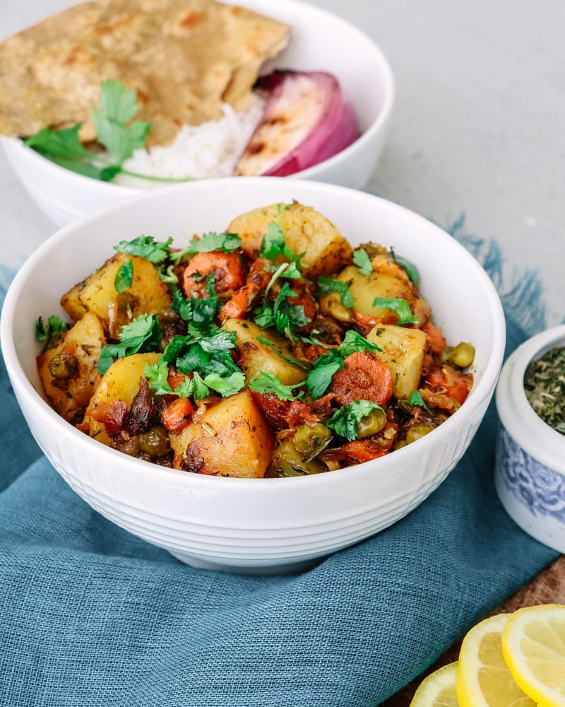 Easy Mixed Vegetable Curry with potatoes, carrots, and peas topped with cilantro and served with roti and rice.