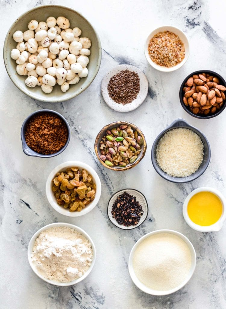 Ingredients for Panjeeri such as nuts, seeds, dry fruit, semolina, flour,placed in individual bowls.