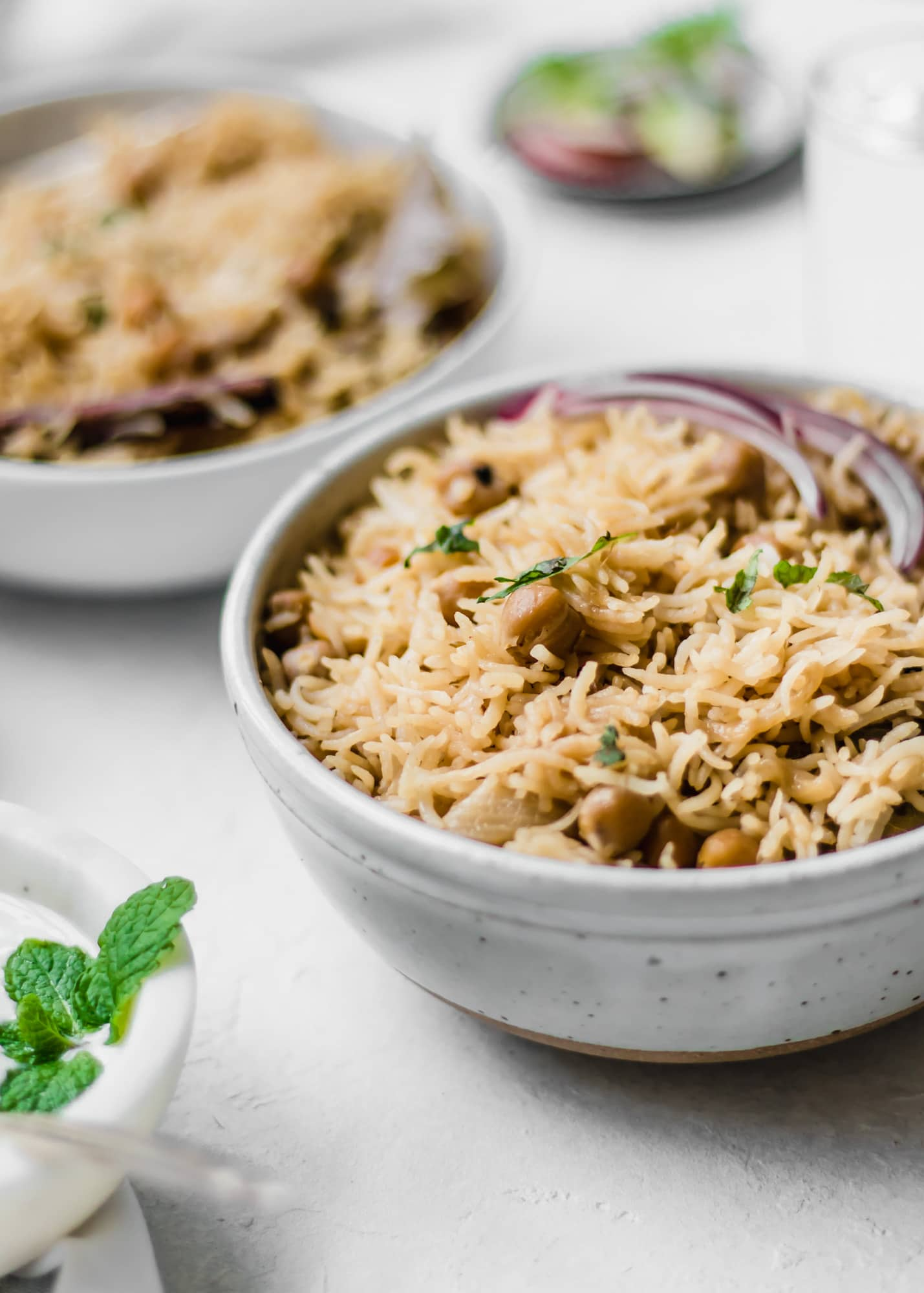 Chana Pulao (chickpea pilaf) in a white bowl with sliced red onions