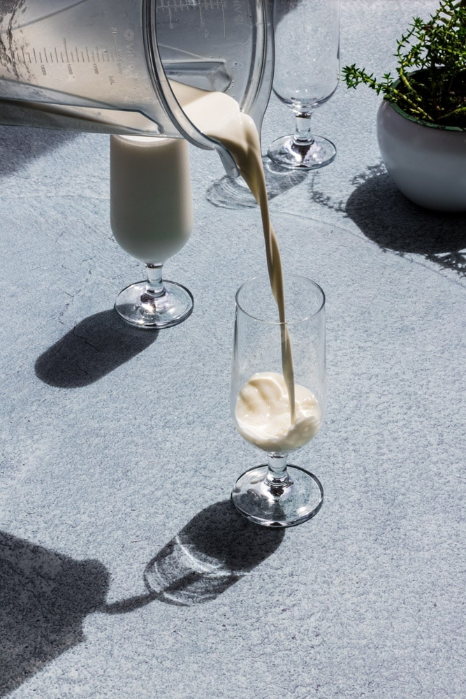 Pouring lassi drink from a blender onto a clear glass