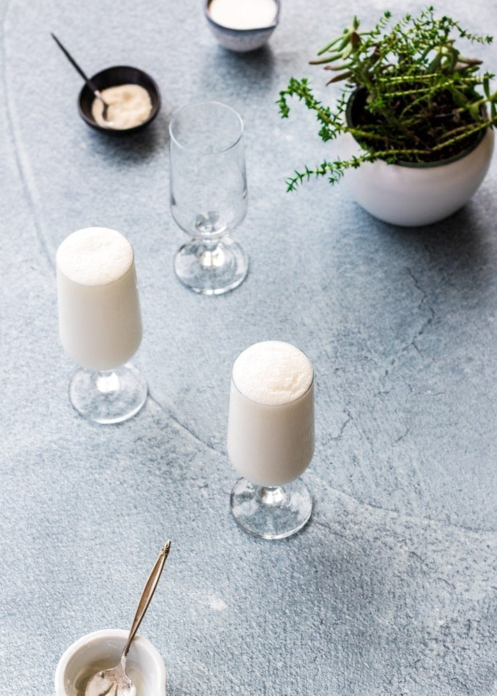 Lassi drink in tall, clear glasses with sugar and a plant in the scene