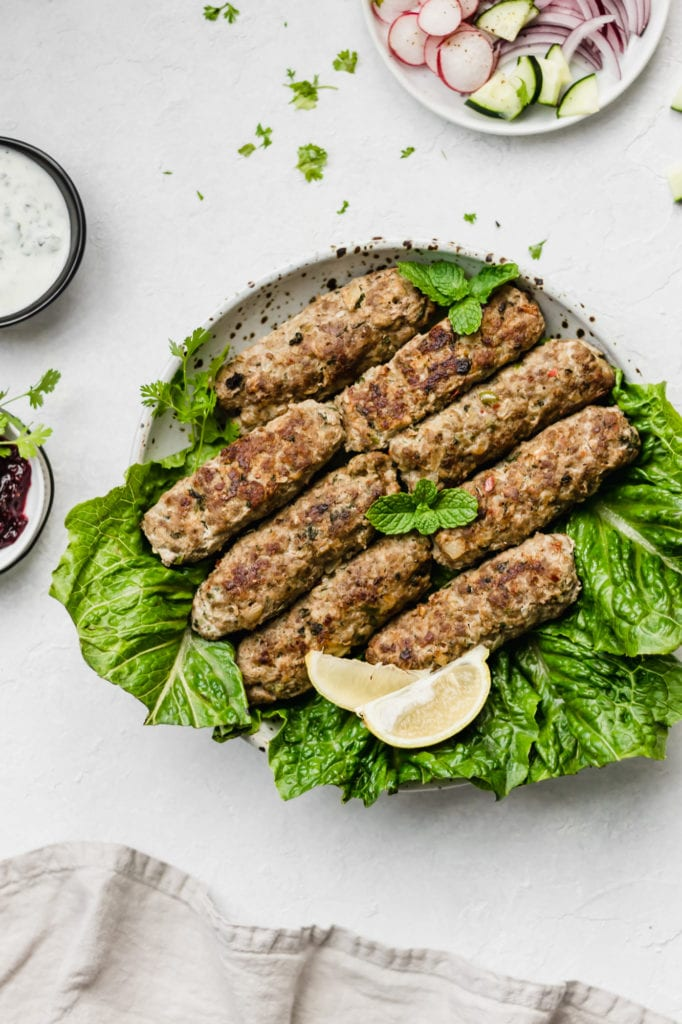 Pakistani Baked Seekh Kabob on top of a bed of lettuce garnished with mint leaves and a lemon wedge.