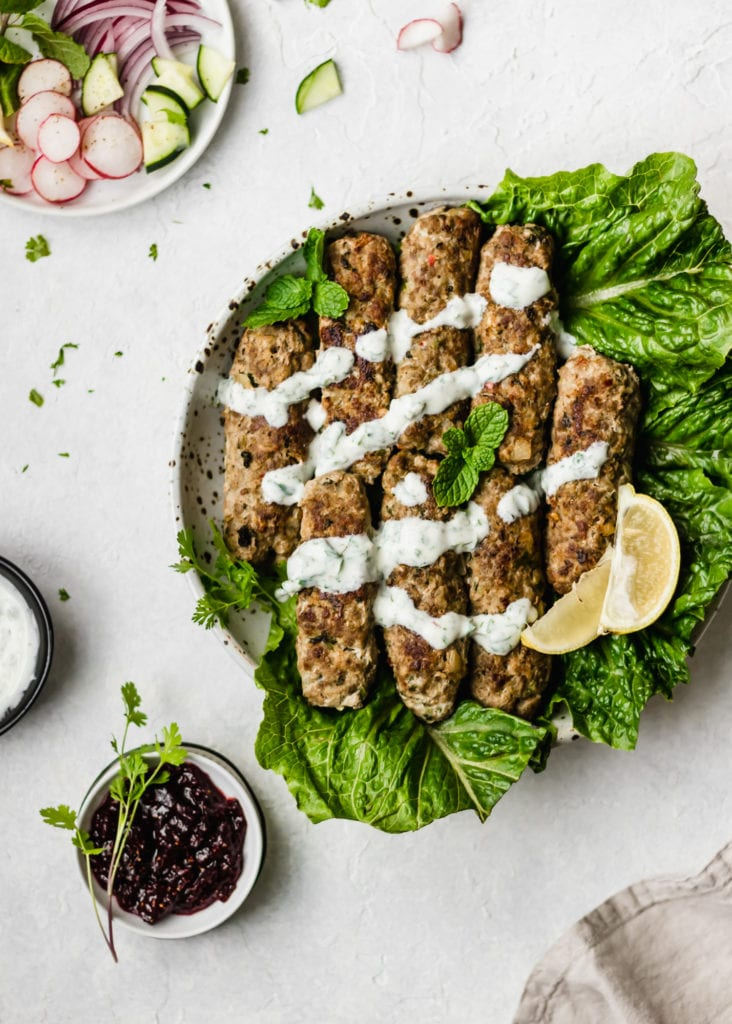 A plate of Oven Baked Pakistani Seekh Kabob on a bed of lettuce,drizzled with yogurt raita, garnished with cilantro and a wedge of lemon. Served with a small bowl of fig chutney.
