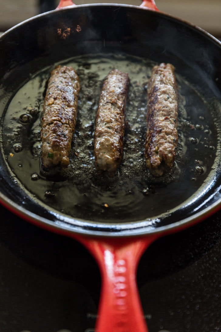 Pan-frying seekh kebab in a red cast iron skillet