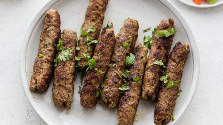 Seekh Kebab garnished with cilantro on a white plate