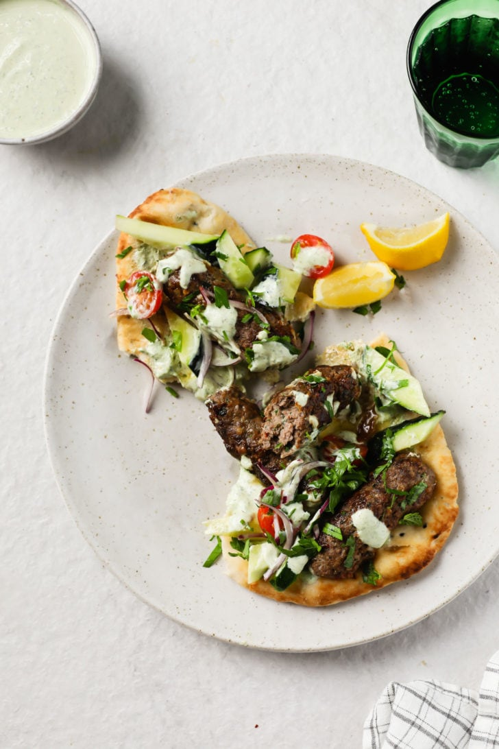 Seekh Kebab on Naan garnished with crunchy vegetables and mint chutney