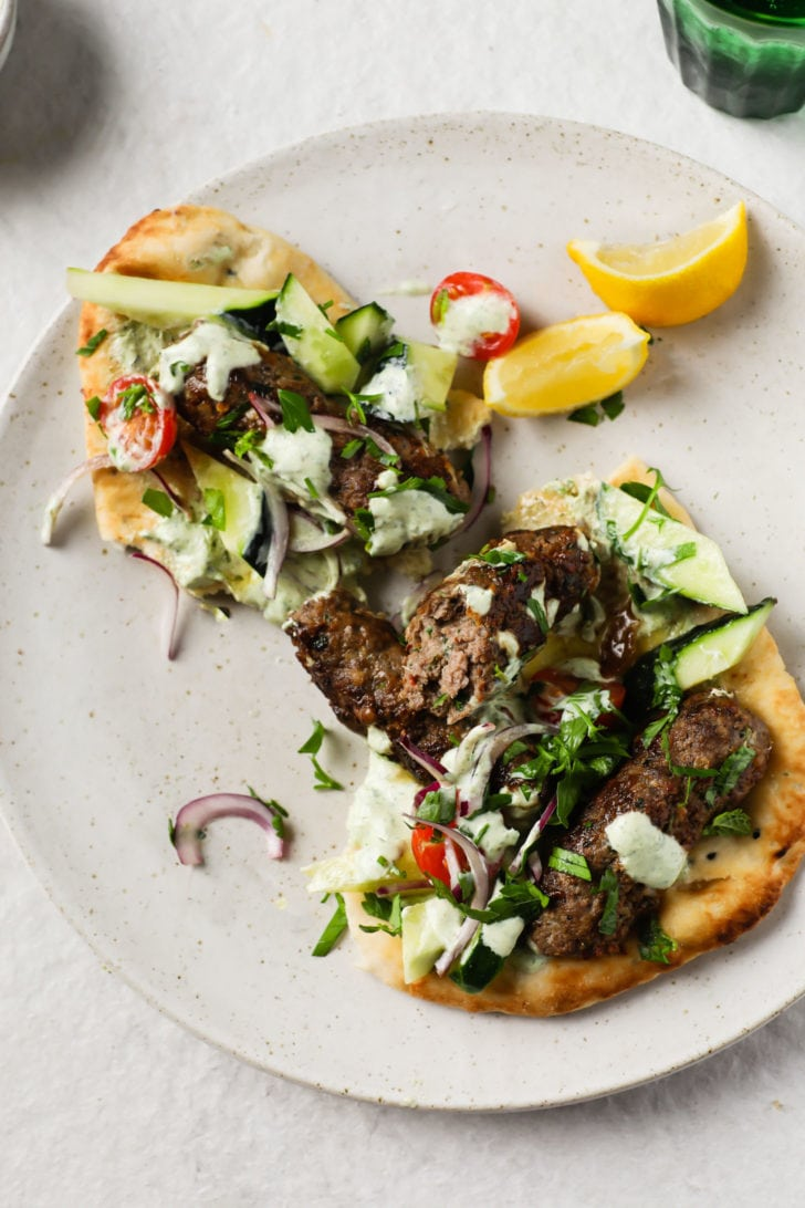 Seekh Kebab on Naan garnished with crunchy vegetables and served with lime