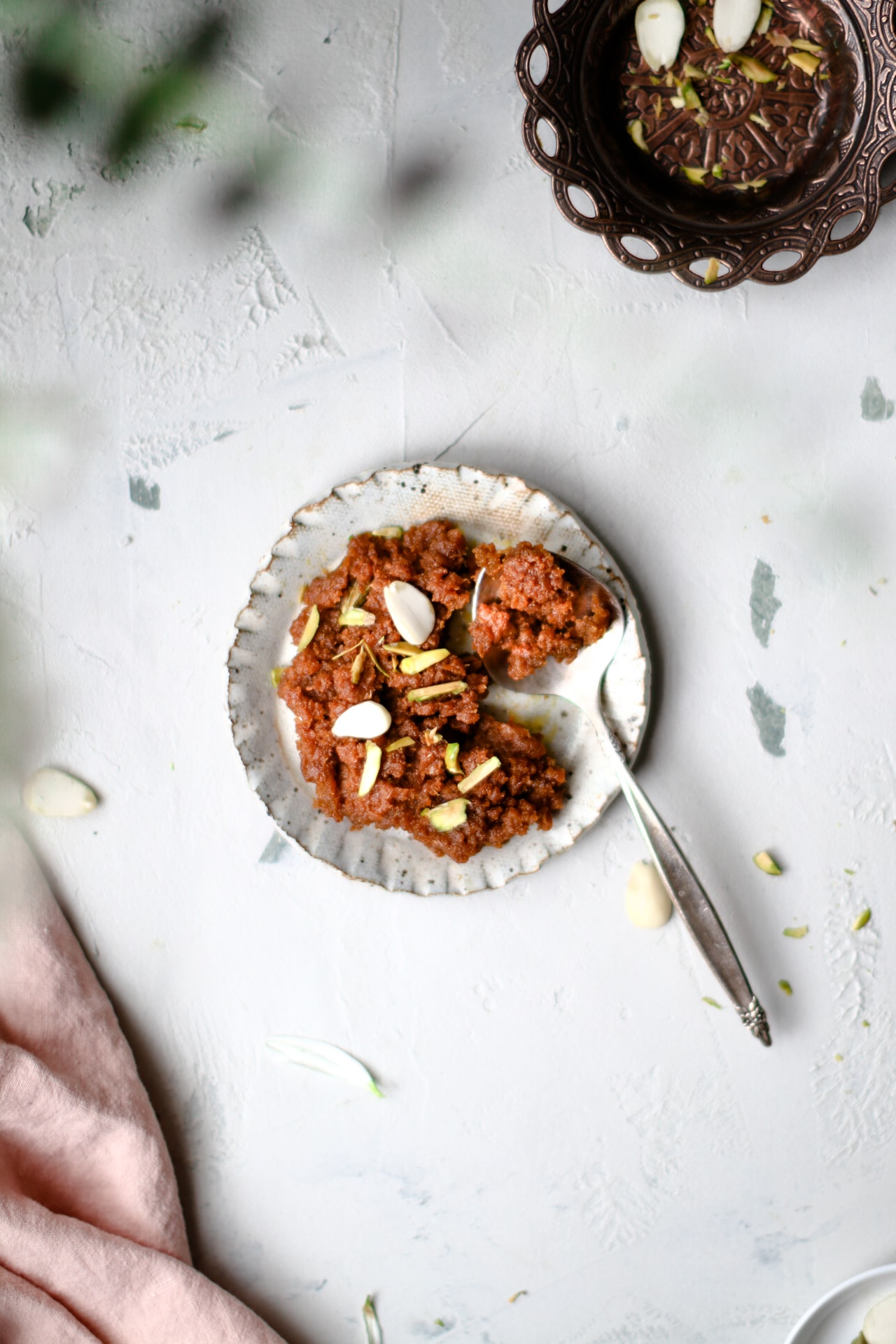 Top view of Instant Pot Carrot Halwa on a small plate with a silver spoon.