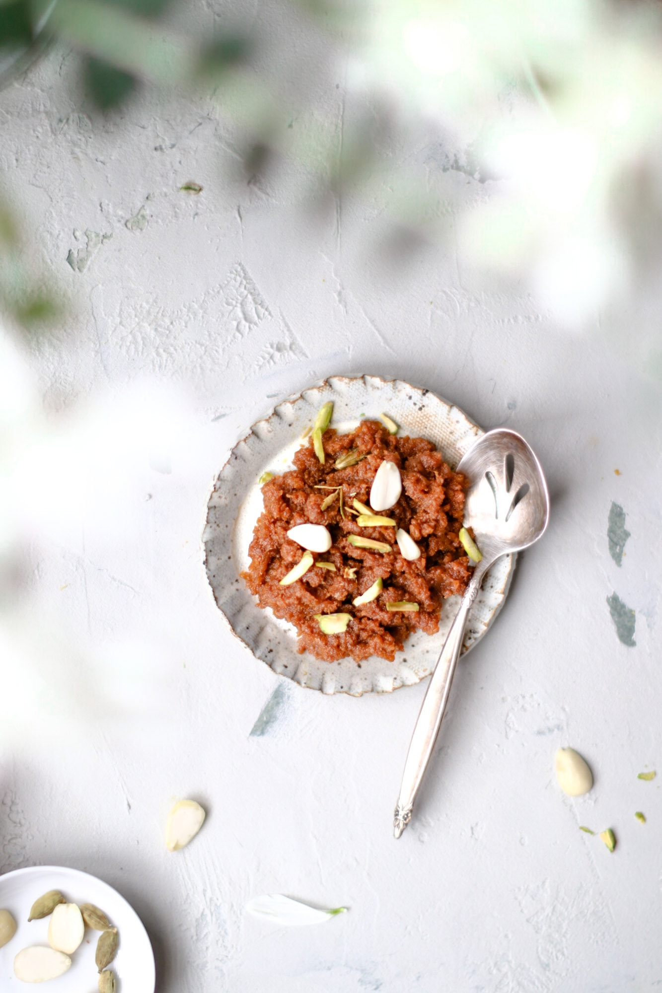 Close up of a plate of Instant Pot Carrot Halwa with a silver spoon on the side.