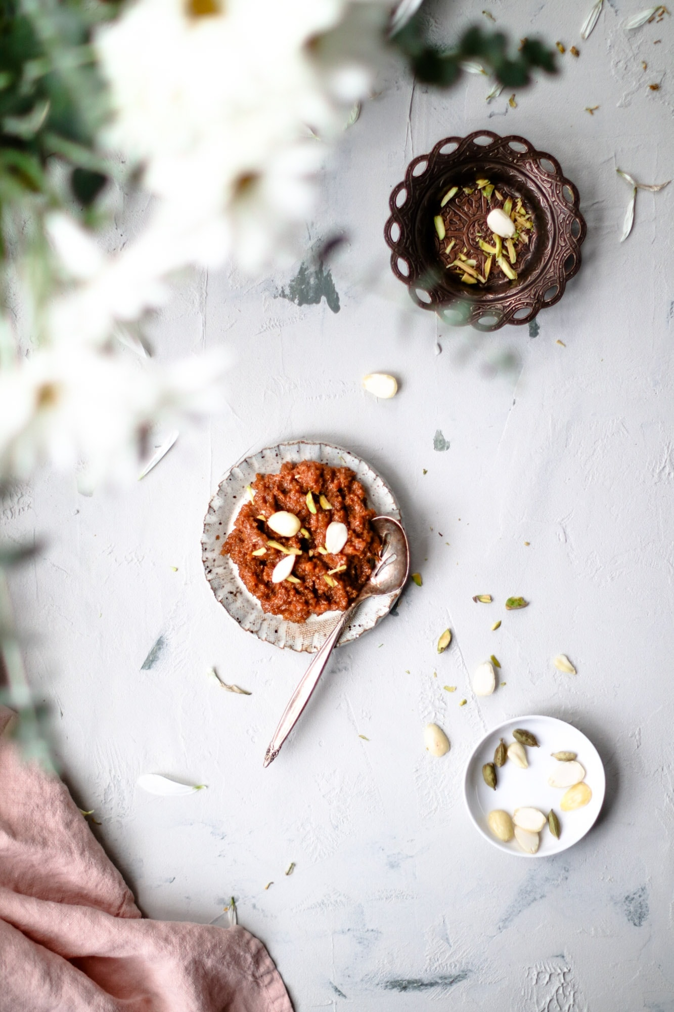 Top view of Instant Pot Carrot Halwa on a small place with a silver spoon garnished with sliced almonds and pistachios.