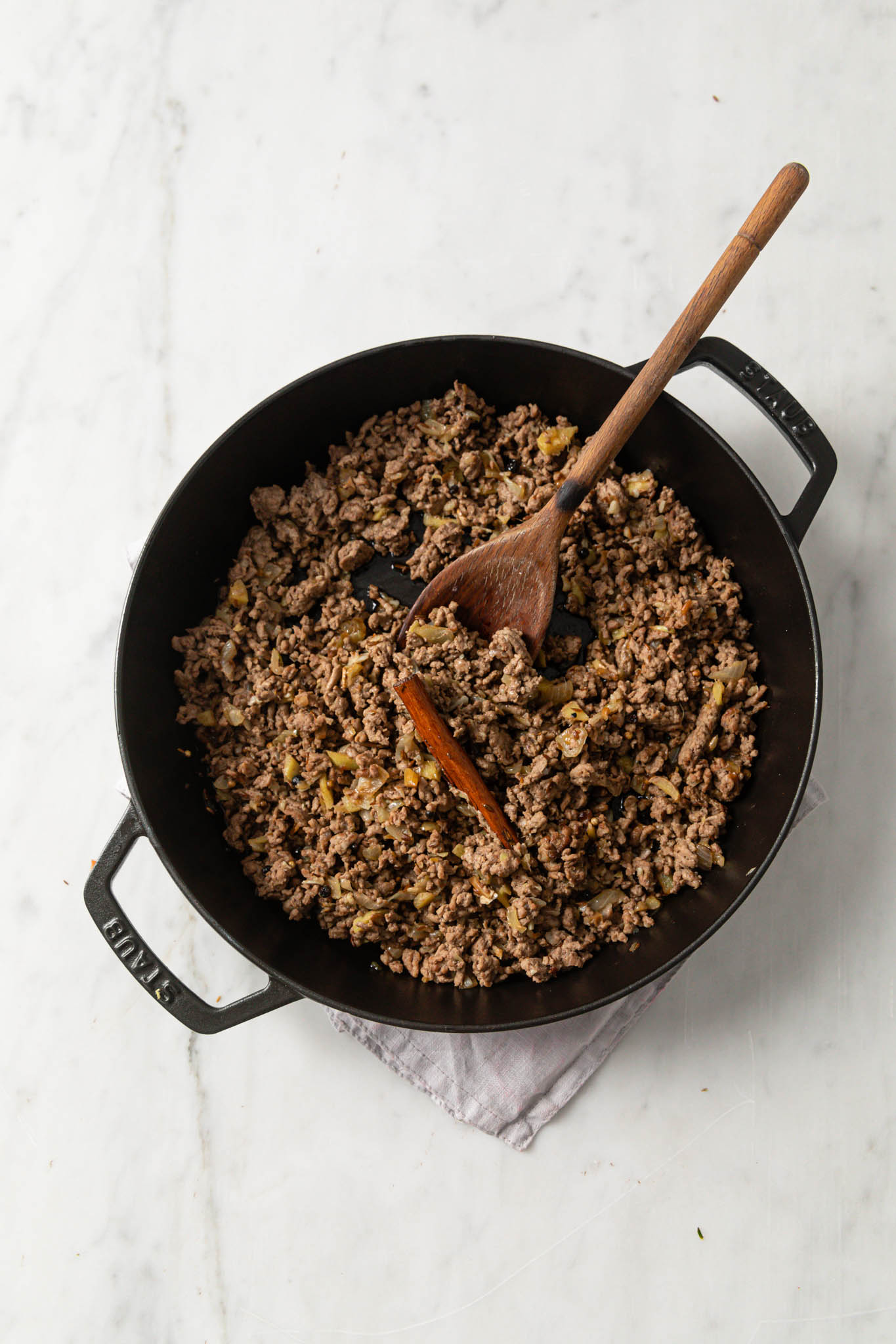 Keema curry in a black pan with a wooden spoon