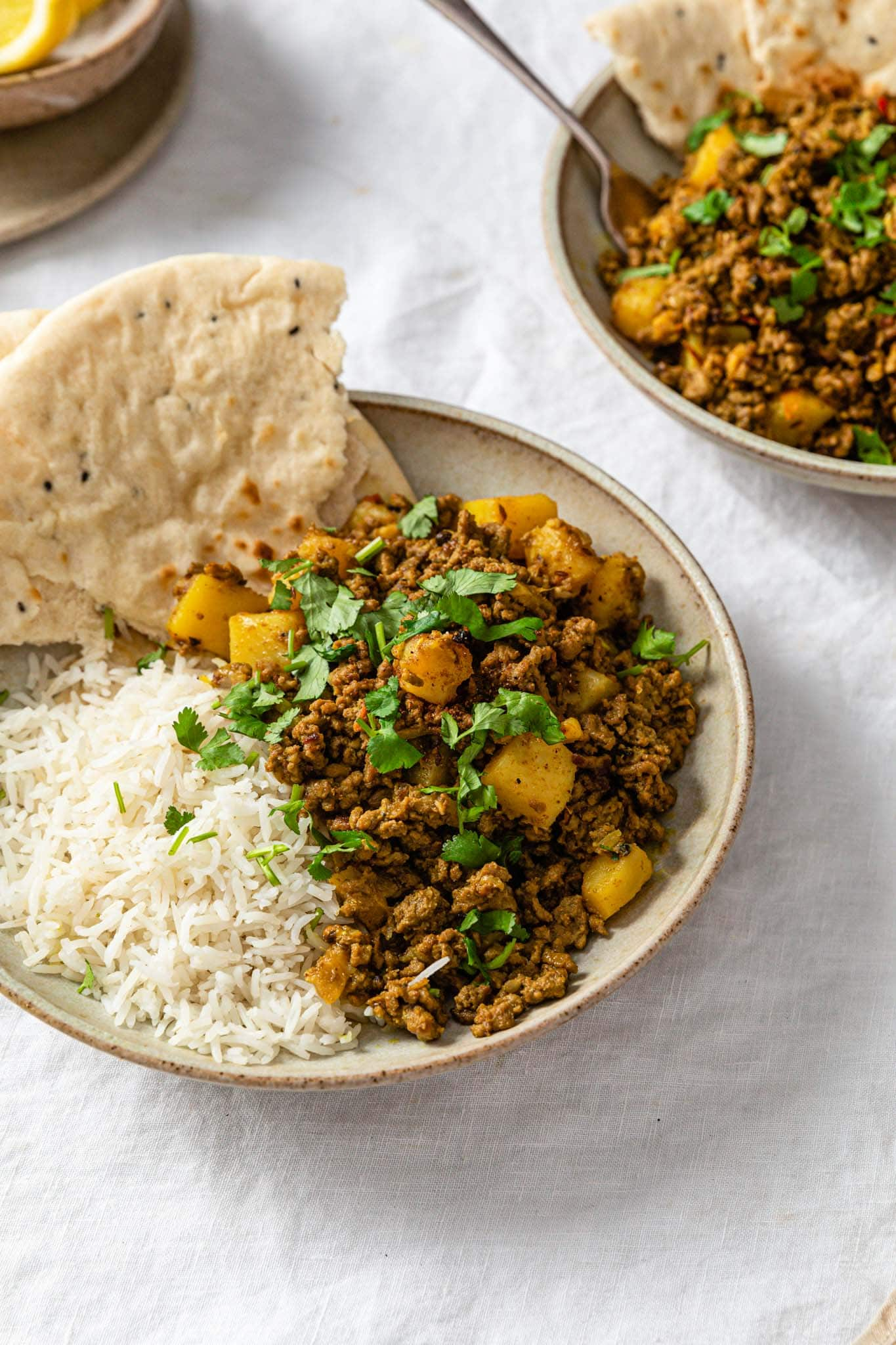 Side shot of Aloo Keema (ground beef and potato curry) in a beige bowl