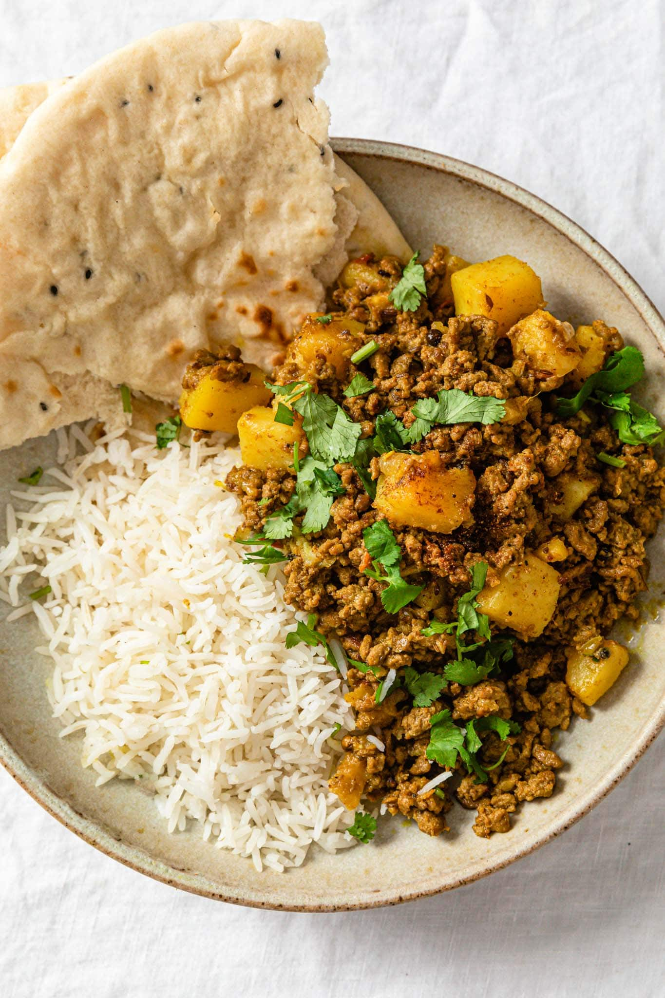 Ground beef and potato curry in a beige bowl with basmati rice and naan