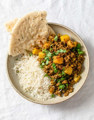 Aloo Keema (Ground Beef and potato curry) in a bowl with basmati rice and naan.
