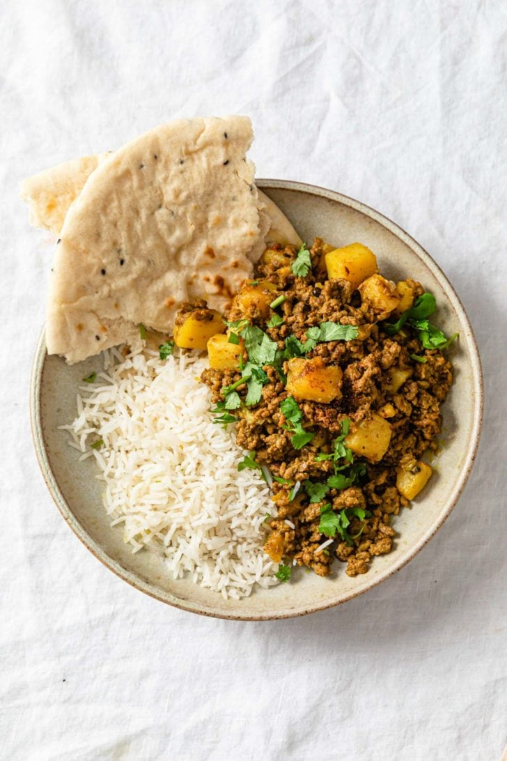 Aloo Keema (Ground Beef and Potato Curry) in a beige bowl served with naan and rice and garnished with cilantro