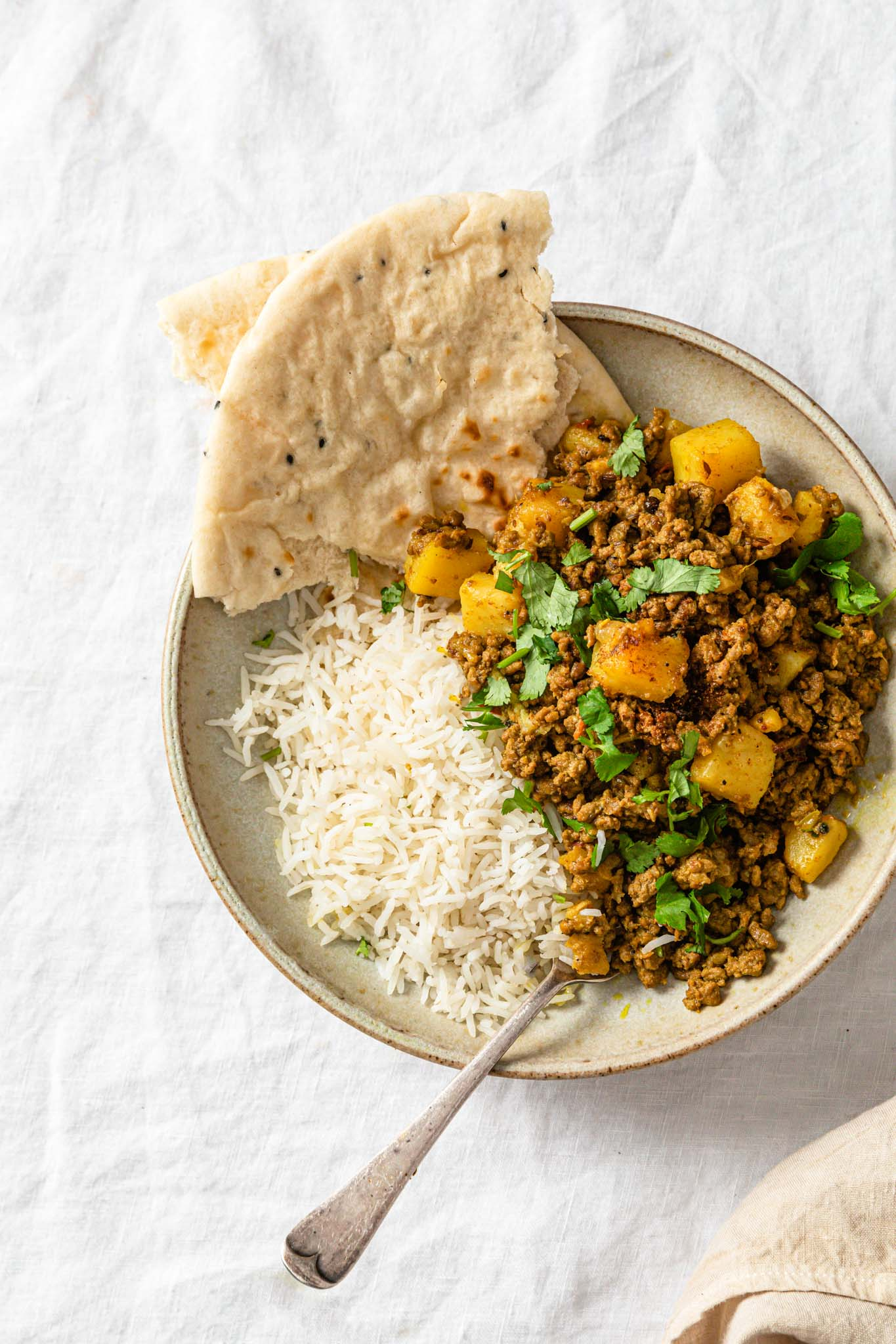Aloo Keema in a bowl with basmati rice and naan with a silver spoon