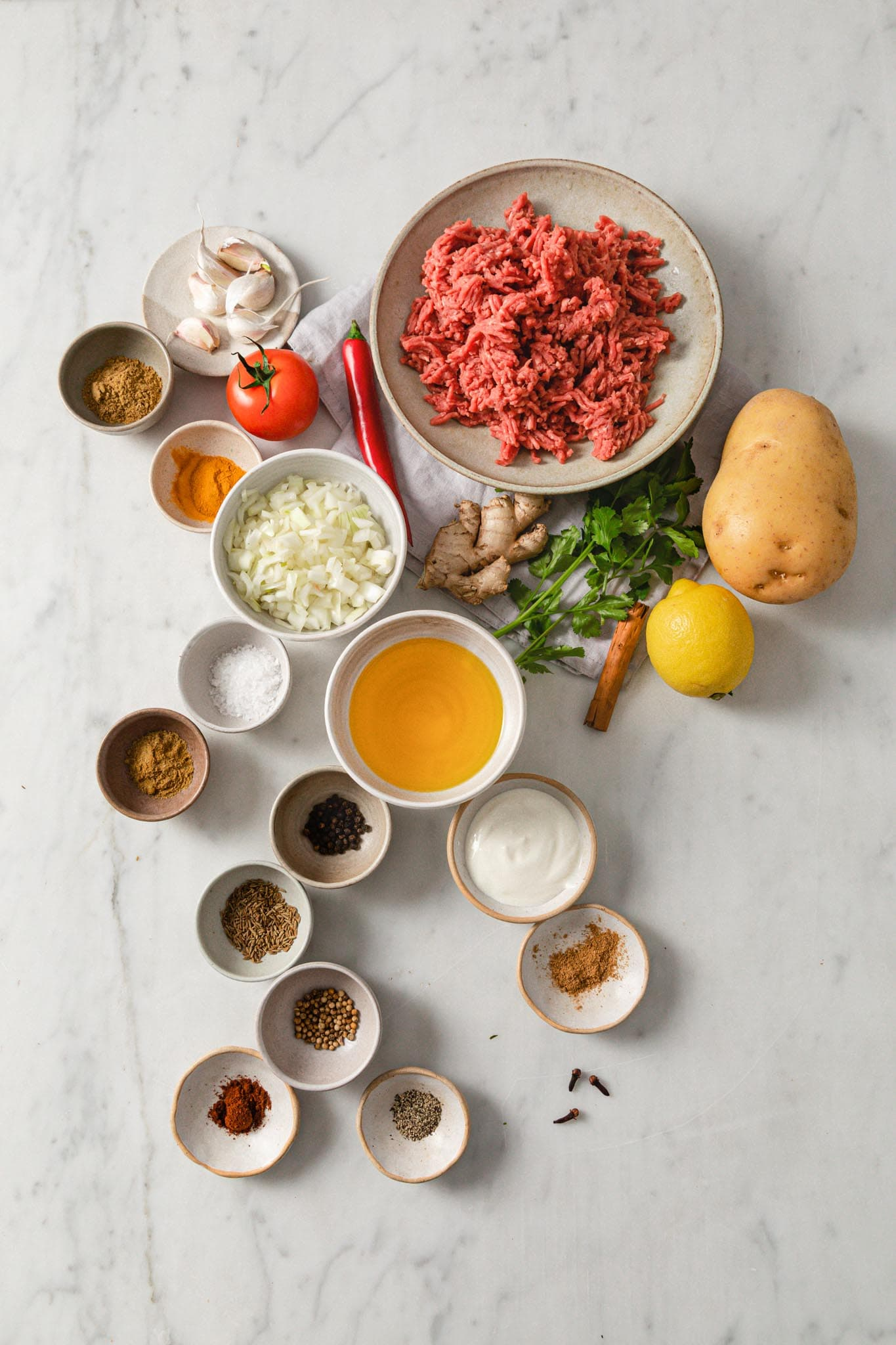 A marble top with ingredients for making Aloo Keema