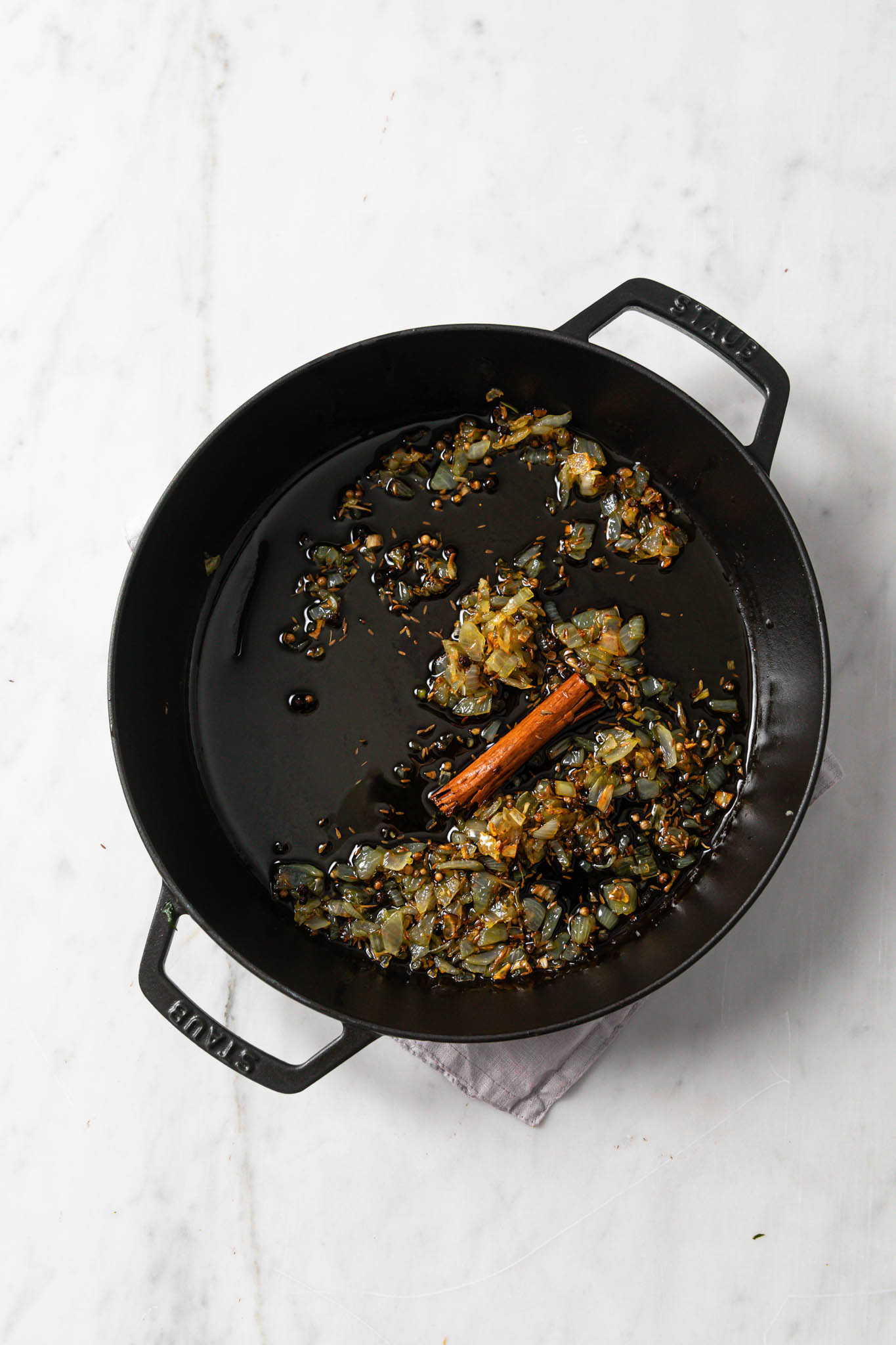 A black skillet with browned onions and whole spices in preparation for keema aloo